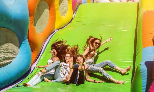 Gorgeous girls having fun on a slide on a sunny day