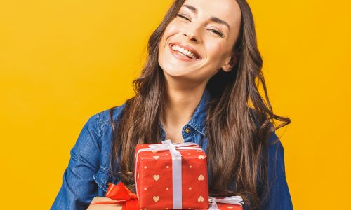Young smiling model hold gift box woman isolated on yellow back