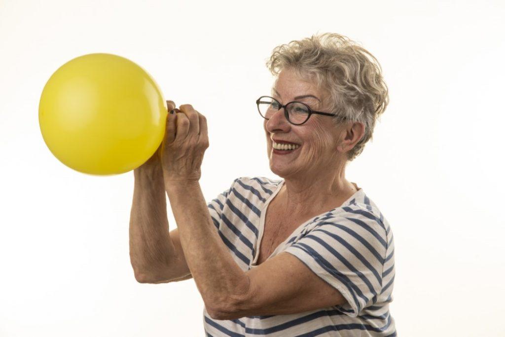 Aeltere frau mit gelben luftballon